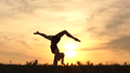 Girl dancer at sunset performs a handstand - slow motion. 71869189