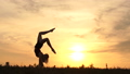Amazing girl acrobat at sunset performs handstand - slow motion. 71869190