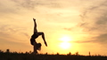 Amazing acrobat at sunset performs handstand - slow motion. 71869193
