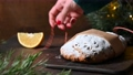 Unwrapping and cutted Christmas stollen or guests in festive setting near the Christmas tree. 72108587