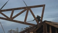Construction work. Installation of a wooden truss on the roof of a private house. The worker turns the farm around. 72177281