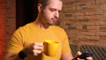 Man texting or browsing online using smartphone and drinking tea or coffee 72179176