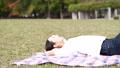 公園で寝転んでリラックスする女性 72198965
