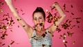 Super Slow Motion of Excited Brunette Woman with falling confetti dancing and jumping, having fun. 72222877