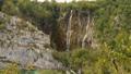 People walk on boardwalk near rock towards waterfalls. Plitvice Lakes from above, Croatia 72236842
