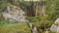 Tourists on wooden path leading to high waterfall. Plitvice Lakes from above, Croatia 72236843