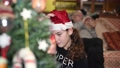Young girl at home decorating Christmas Tree wearing Santa Hat with grandpa on the background 72297961