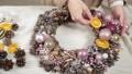 Woman florist makes new year wreaths. 72336661