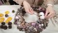 Woman florist makes new year wreaths. 72336666