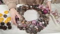 Woman florist makes new year wreaths. 72336667