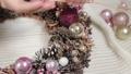 Woman florist makes new year wreaths. 72336669