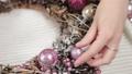 Woman florist makes new year wreaths. 72336672