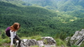 active girl hiker looking a the mountains panorama standing on a edge of rock 72360678