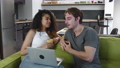 Happy multiracial young couple talking and using laptop together watching video sitting on sofa in living room. Caucasian man and african american woman looking at computer at home. 72390366