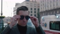 Successful young businessman putting on sunglasses and looking confidently outdoors in the city. Handsome entrepreneur in suit standing street urban looking confident. Camera rotates, steadicam shot. 72403135