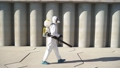 Cleaner with pressurized sprayer in hands going to disinfect public places. 72451761