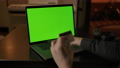 Dolly in shot of chromakeyed laptop screen and man's hands with credit card. 72575811