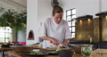 Caucasian female chef preparing a dish and smiling in a kitchen  72614996