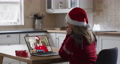 Caucasian woman wearing santa hat on laptop video chat during christmas at home 72615289