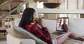 Mixed race woman on laptop video chat having coffee during christmas at home 72615290