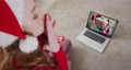 Caucasian woman wearing santa hat on laptop video chat during christmas at home 72615292