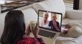 Mixed race woman on laptop video chat having coffee during christmas at home 72615293