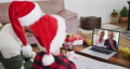 Caucasian man with son wearing santa hats on laptop video chat during christmas at home 72615294