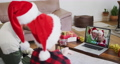 Caucasian man with son wearing santa hats on laptop video chat during christmas at home 72615295