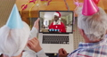 Caucasian senior couple wearing party hats on laptop video chat during christmas at home 72615296