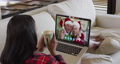 Mixed race woman on laptop video chat having coffee during christmas at home 72615297