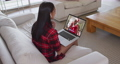 Mixed race woman on laptop video chat wearing wireless earphones during christmas at home 72615298