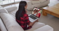 Mixed race woman on laptop video chat wearing wireless earphones during christmas at home 72615300