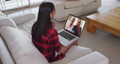 Mixed race woman on laptop video chat wearing wireless earphones during christmas at home 72615301