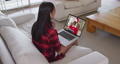 Mixed race woman on laptop video chat wearing wireless earphones during christmas at home 72615302