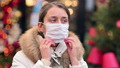 Woman wearing white medical mask at the christmas market with decorations smiling 72731540