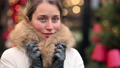 Woman wearing white winter coat at the christmas market with decorations smiling 72731542