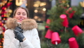 Woman wearing white winter coat at the christmas market with decorations smiling 72731544