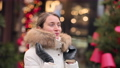 Woman wearing white winter coat freezing at the christmas market with decorations smiling 72731546