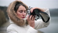 Woman in white winter coat taking photos and shooting video on a vintage camera 72731551
