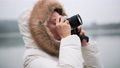 Woman in white winter coat taking photos and shooting video on a vintage camera 72731553