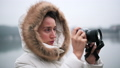 Woman in white winter coat taking photos and shooting video on a vintage camera 72731556