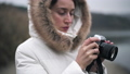Woman in white winter coat taking photos and shooting video on a vintage camera 72731559