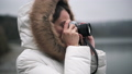 Woman in white winter coat taking photos and shooting video on a vintage camera 72731562