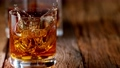 Pouring whiskey on vintage wooden table in super slow motion. 73142181