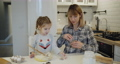 Young mother and daughter having fun baking cookies in the kitchen together 73166814