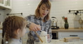 Young mother and daughter having fun baking cookies in the kitchen together 73166816
