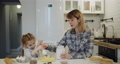 Young mother and daughter having fun baking cookies in the kitchen together 73166817