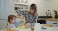 Young mother and daughter having fun baking cookies in the kitchen together 73166818