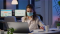 Employee with protection face mask working late at night in new normal office 73199569