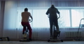 Silhouettes of two men exercising on stationary bikes. 73242656